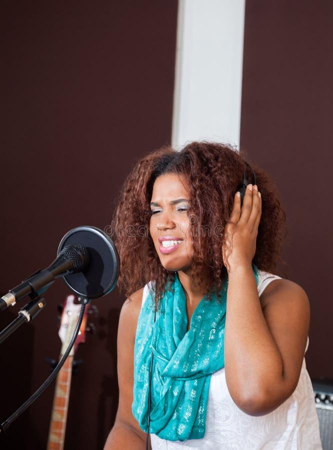 Mujer que canta mientras que escucha la música a través foto de archivo libre de regalías