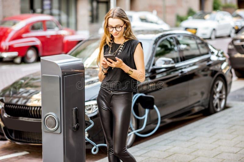 Mujer que carga el coche eléctrico al aire libre fotos de archivo libres de regalías
