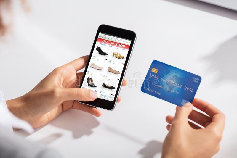 Mujer que celebra compras en línea que hacen disponibles de la tarjeta de crédito foto de archivo