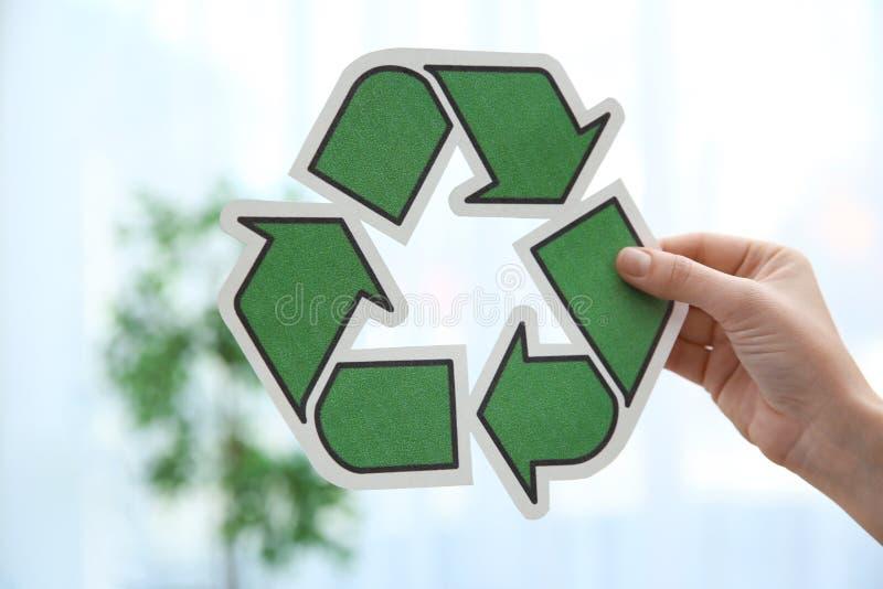 Mujer que celebra el reciclaje de símbolo en fondo borroso fotografía de archivo