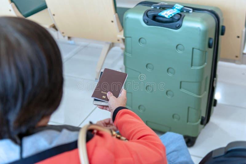Mujer que celebra pasaportes y el teléfono con la maleta en el aeropuerto foto de archivo libre de regalías