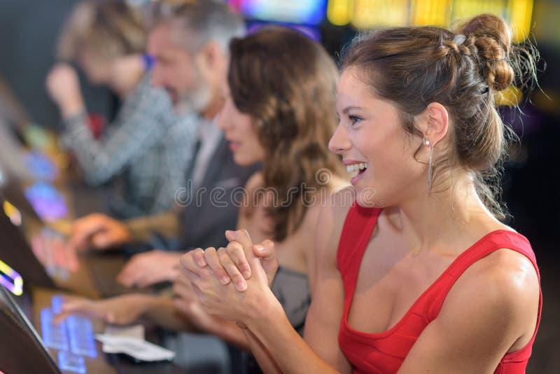 Mujer que celebra triunfo en la máquina tragaperras en el casino imagenes de archivo