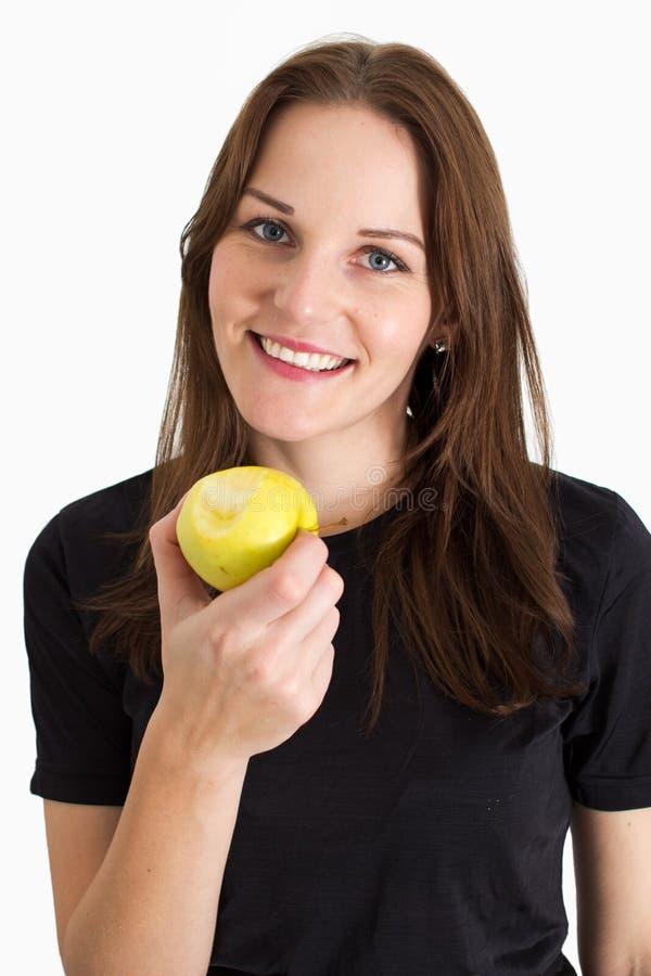 Mujer que celebra un Apple y una sonrisa amarillos imagenes de archivo