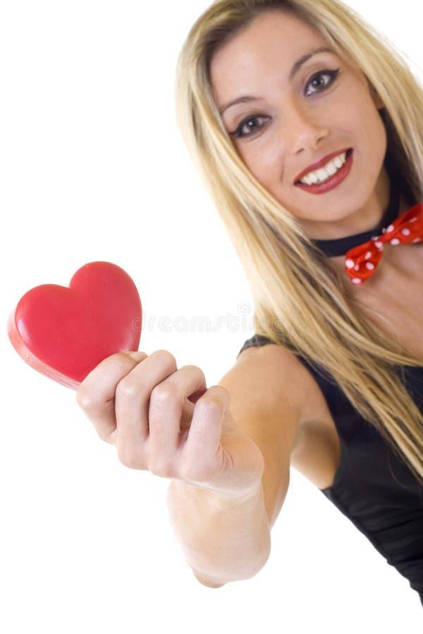 Mujer que celebra un corazón y una sonrisa rojos grandes fotografía de archivo libre de regalías
