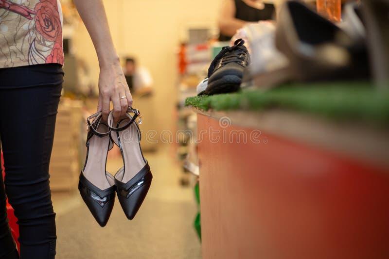 Mujer que celebra un par de zapatos en su mano en la zapatería fotografía de archivo