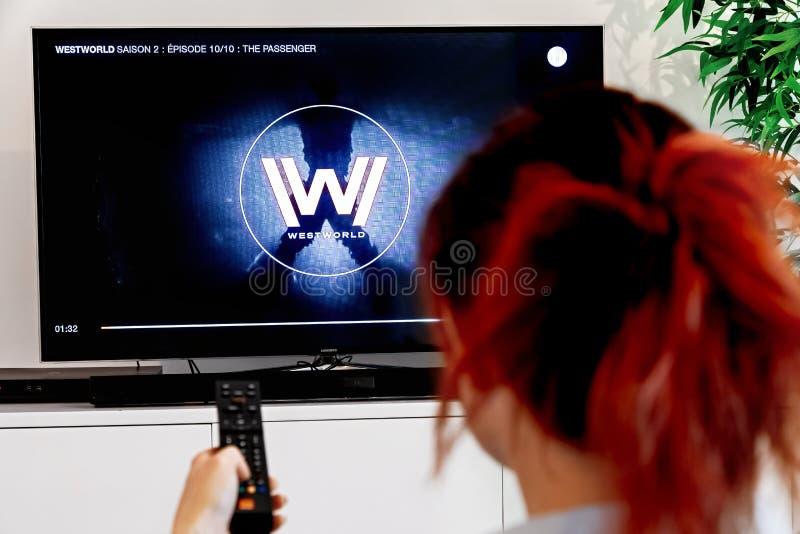 Mujer que celebra un telecontrol y un reloj Westworld, una creación original de la TV de la industria de HBO Westworld foto de archivo libre de regalías