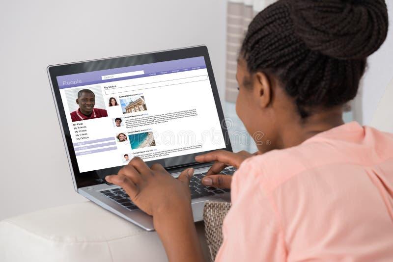 Mujer que charla en sitio social del establecimiento de una red foto de archivo