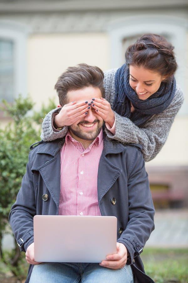 Mujer que cierra los ojos de su hombre fotos de archivo