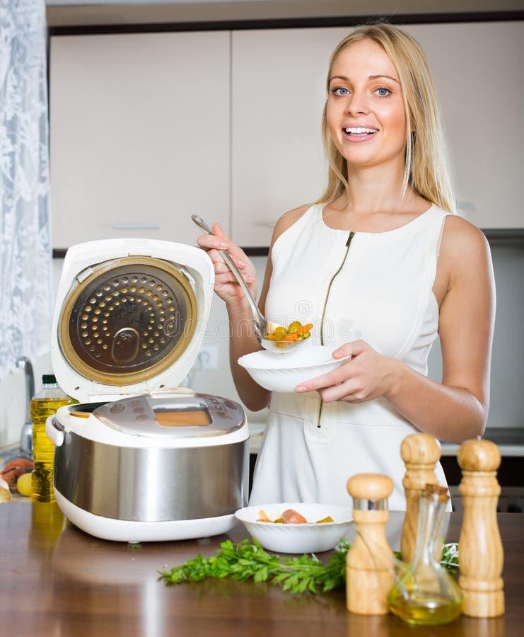 Mujer que cocina con el multicooker foto de archivo