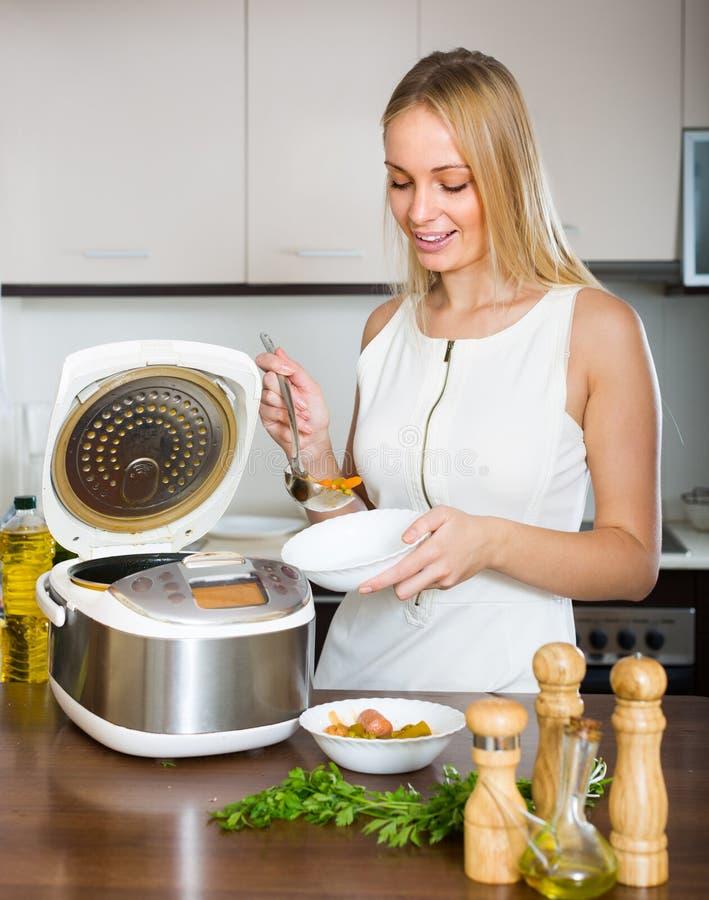 Mujer que cocina con el multicooker fotografía de archivo libre de regalías