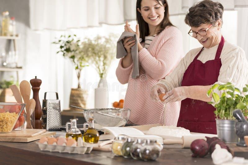 Mujer que cocina con la nieta imagen de archivo