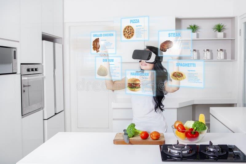Mujer que cocina con los vidrios de la realidad virtual imágenes de archivo libres de regalías