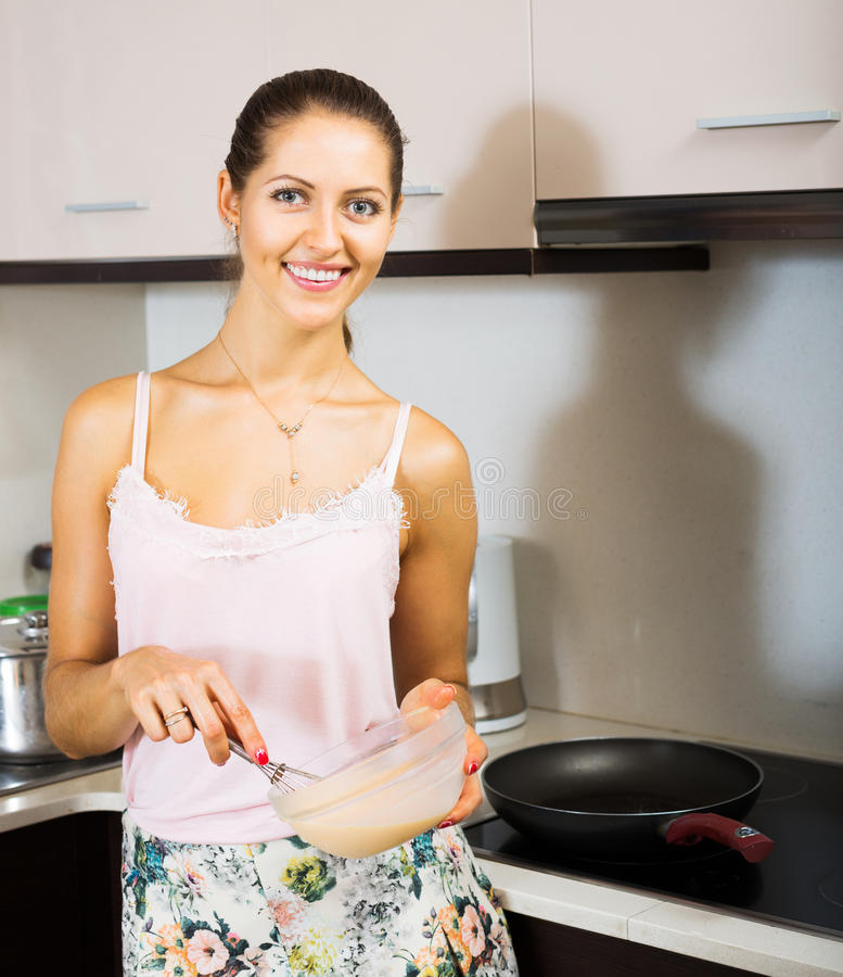 Mujer que cocina el soplo del huevo imagen de archivo