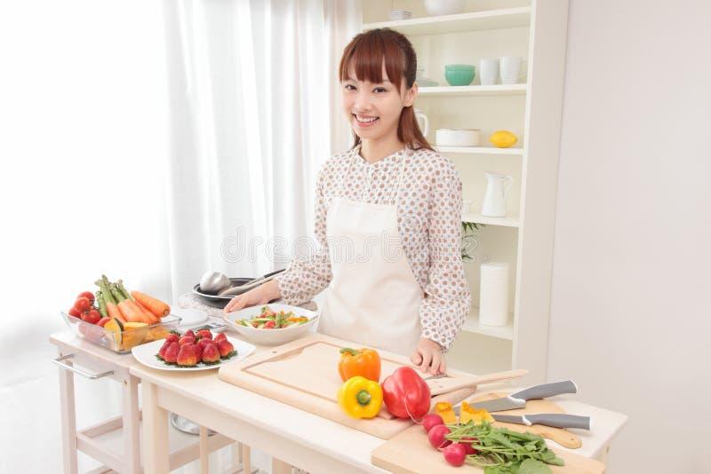 Mujer que cocina en cocina fotografía de archivo libre de regalías