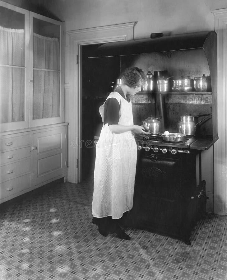 Mujer que cocina en cocina (todas las personas representadas no son vivas más largo y ningún estado existe Garantías del proveedo imagen de archivo libre de regalías