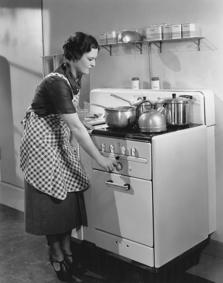Mujer que cocina en estufa fotografía de archivo