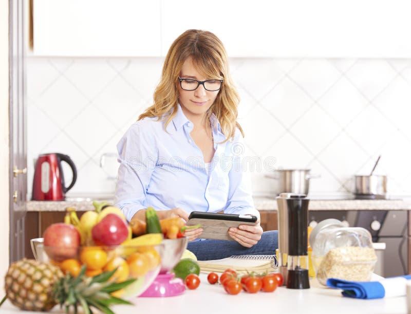 Mujer que cocina en la cocina foto de archivo