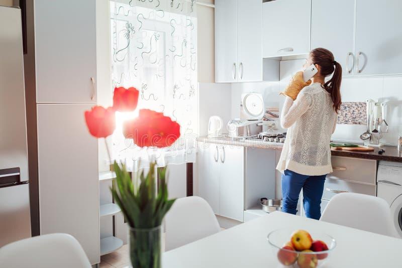 Mujer que cocina la cena en nueva cocina y que habla en el teléfono Diseño moderno de la cocina fotos de archivo libres de regalías