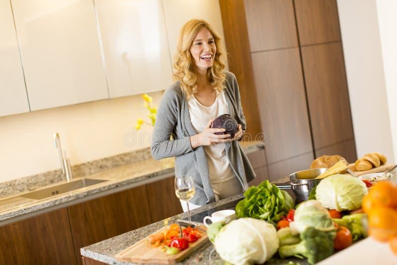 Mujer que cocina la comida sana en la cocina moderna foto de archivo