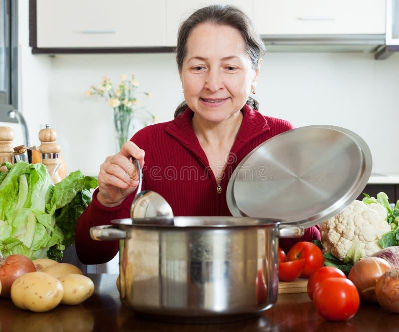 Mujer que cocina la sopa foto de archivo libre de regalías