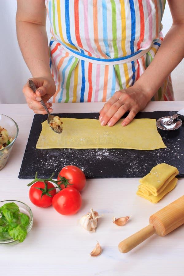 Mujer que cocina los raviolis italianos hechos en casa tradicionales con el relleno de la albahaca y de la salsa y de la patata d imágenes de archivo libres de regalías