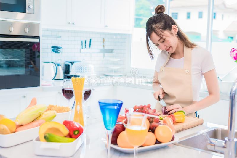 Mujer que cocina y que corta la verdura en sitio de la cocina con lleno de comida y de fruta en la tabla D?a de fiesta y concepto foto de archivo