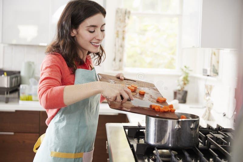 Mujer que cocina zanahorias en la cocina para la comida judía del passover fotos de archivo