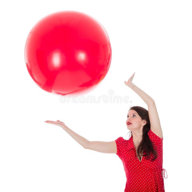 Mujer que coge el globo rojo grande sobre su cabeza imagenes de archivo