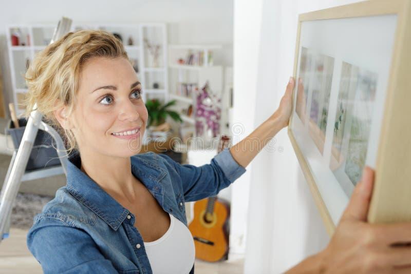 Mujer que coloca el marco en la pared fotografía de archivo libre de regalías
