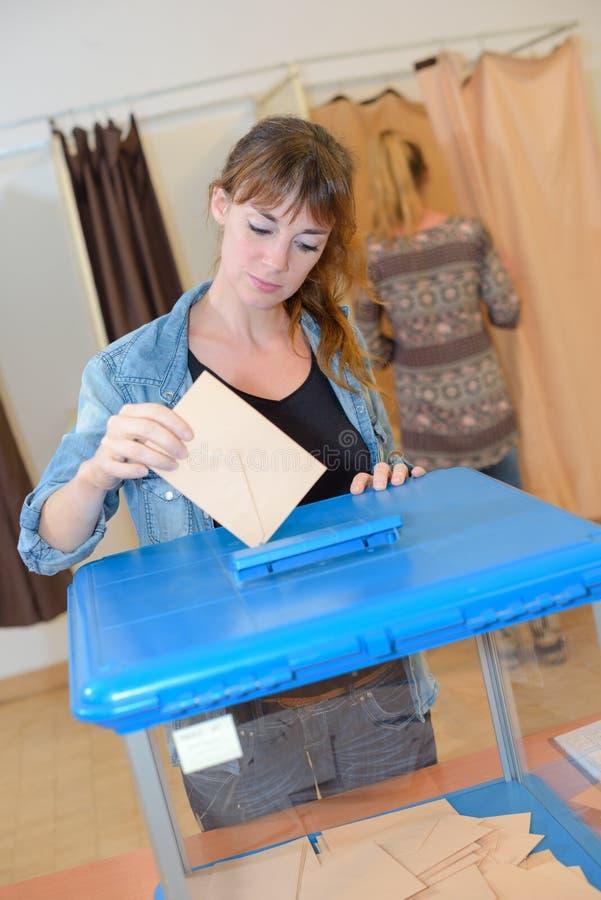 Mujer que coloca el sobre en la urna de votación imagenes de archivo