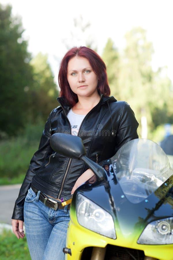 Mujer que coloca la bici cercana fotografía de archivo