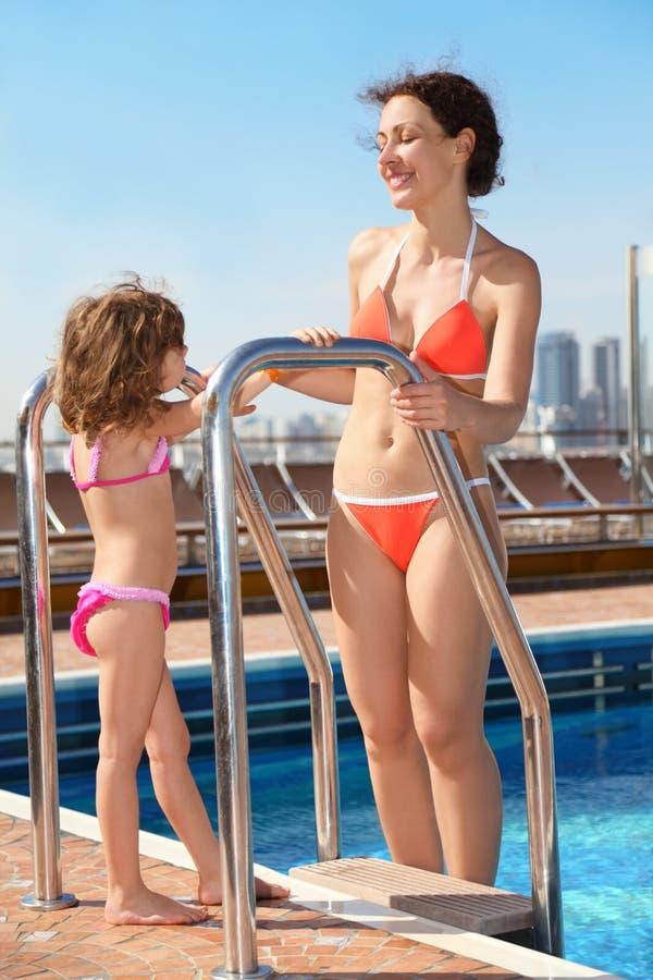 Mujer que coloca la piscina cercana y que mira a la hija fotografía de archivo