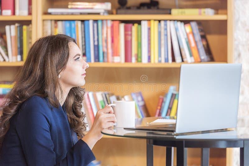 Mujer que come café delante de un ordenador portátil fotos de archivo libres de regalías