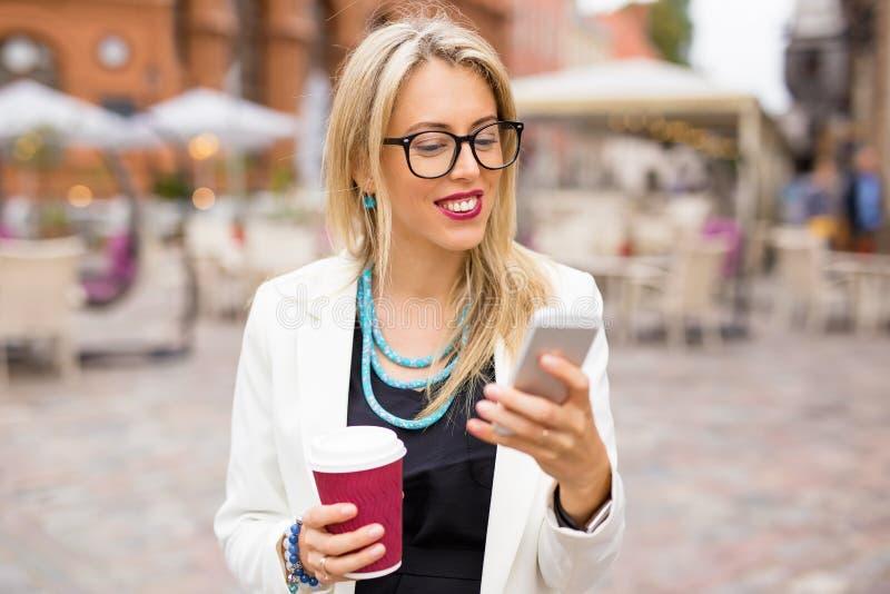Mujer que come café y que usa smartphone imagen de archivo libre de regalías