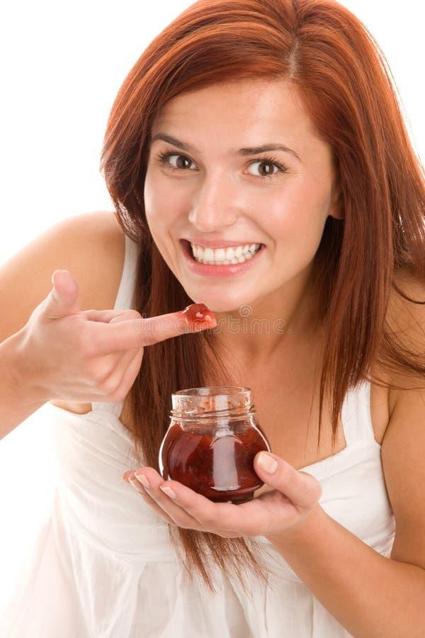 Mujer que come el atasco imagen de archivo