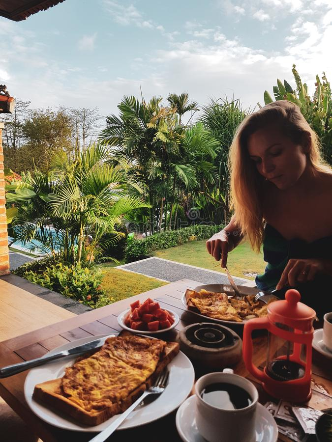Mujer que come el desayuno de la mañana el día de fiesta imagen de archivo
