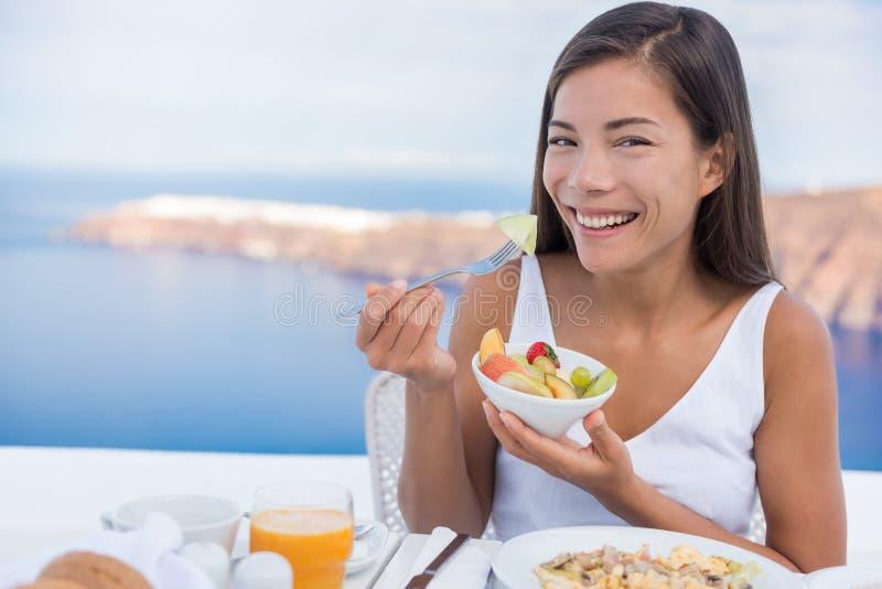 Mujer que come el desayuno sano del cuenco de ensalada de fruta fotos de archivo