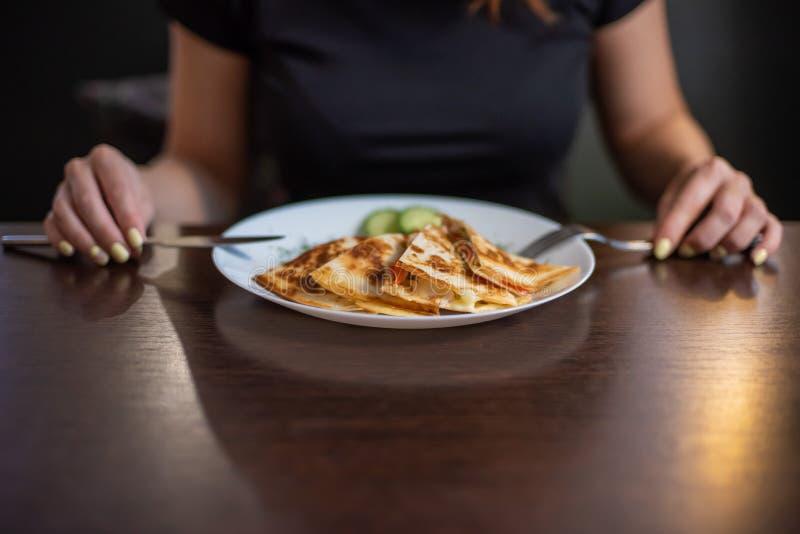 Mujer que come el quesadilla delicioso en restaurante La mujer redheaded joven está comiendo la comida mexicana en un café foto de archivo