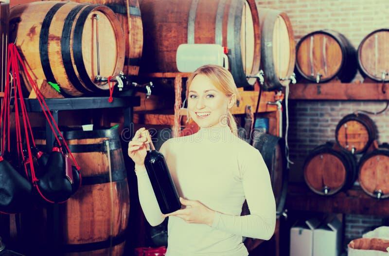 Mujer que come el vidrio de vino en casa del vino imagenes de archivo