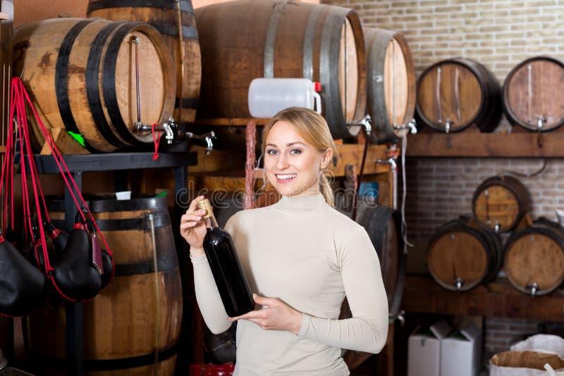 Mujer que come el vidrio de vino en casa del vino foto de archivo