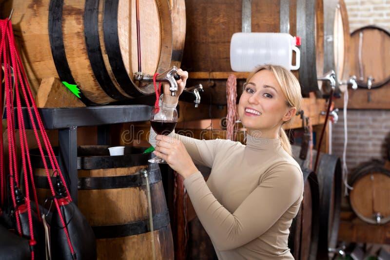 Mujer que come el vidrio de vino en casa del vino imagen de archivo libre de regalías