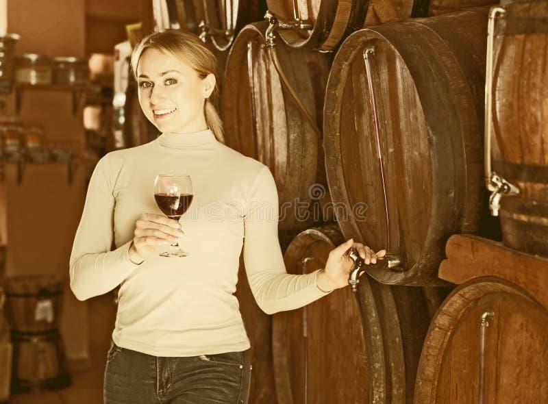 Mujer que come el vidrio de vino en casa del vino fotos de archivo libres de regalías