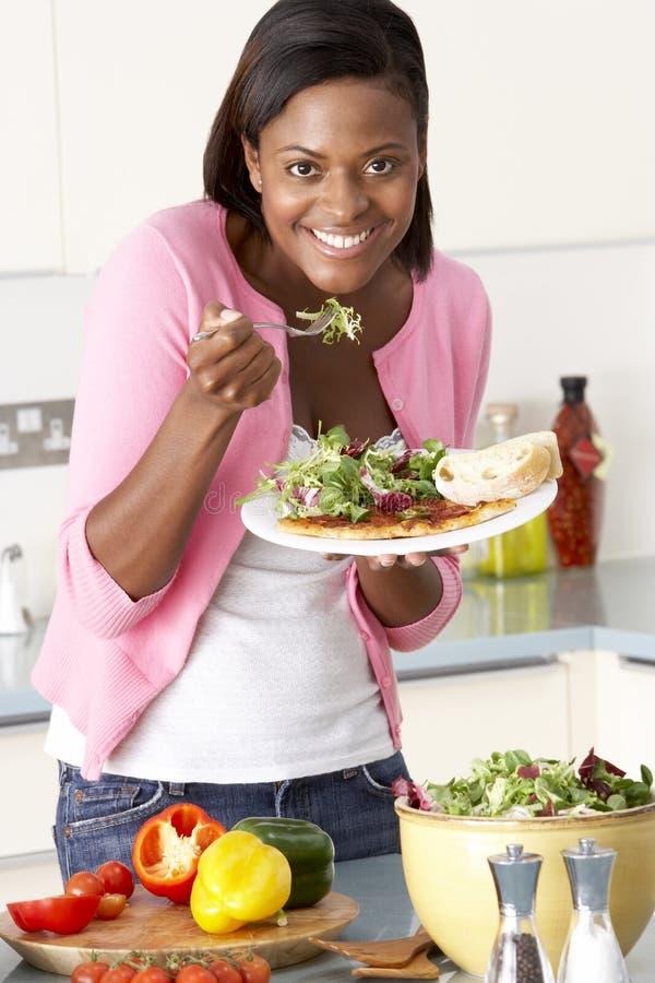Mujer que come la comida en cocina foto de archivo libre de regalías