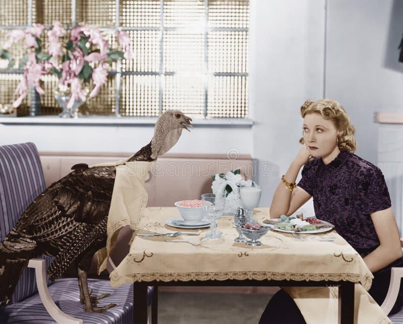 Mujer que come la comida en la tabla con el pavo vivo (todas las personas representadas no están viviendo más de largo y ningún e imagen de archivo libre de regalías