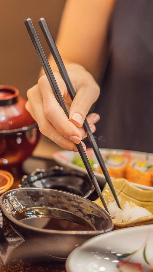 Mujer que come la comida japonesa en un FORMATO VERTICAL del restaurante japonés de la comida para la historia de Instagram o el  imagenes de archivo