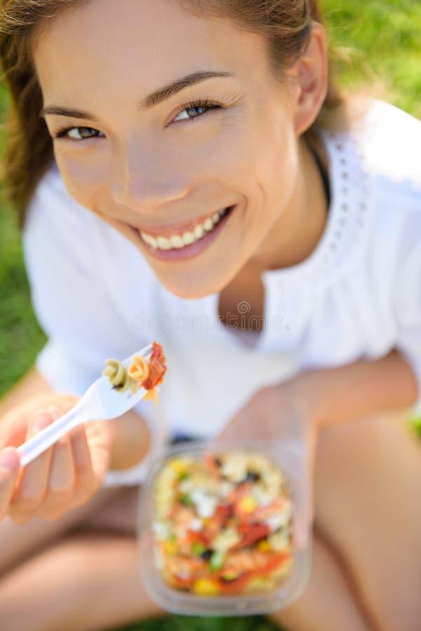 Mujer que come la ensalada de pasta del gluten libremente fotografía de archivo