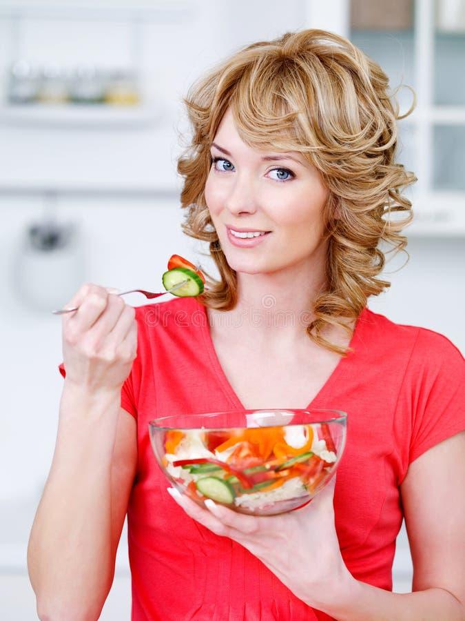 Mujer que come la ensalada heathy en la cocina imagenes de archivo