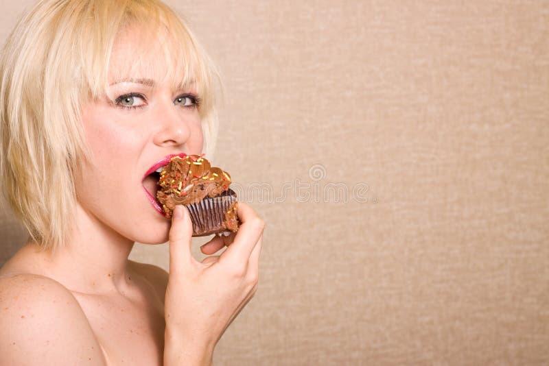 Mujer que come la magdalena del chocolate fotografía de archivo libre de regalías