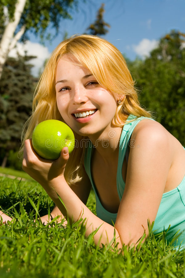 Mujer que come la manzana verde en el claro del verano fotos de archivo libres de regalías
