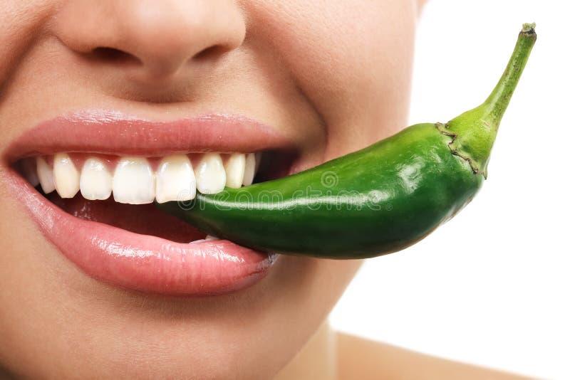 Mujer que come la pimienta sin procesar vegetal verde imagen de archivo